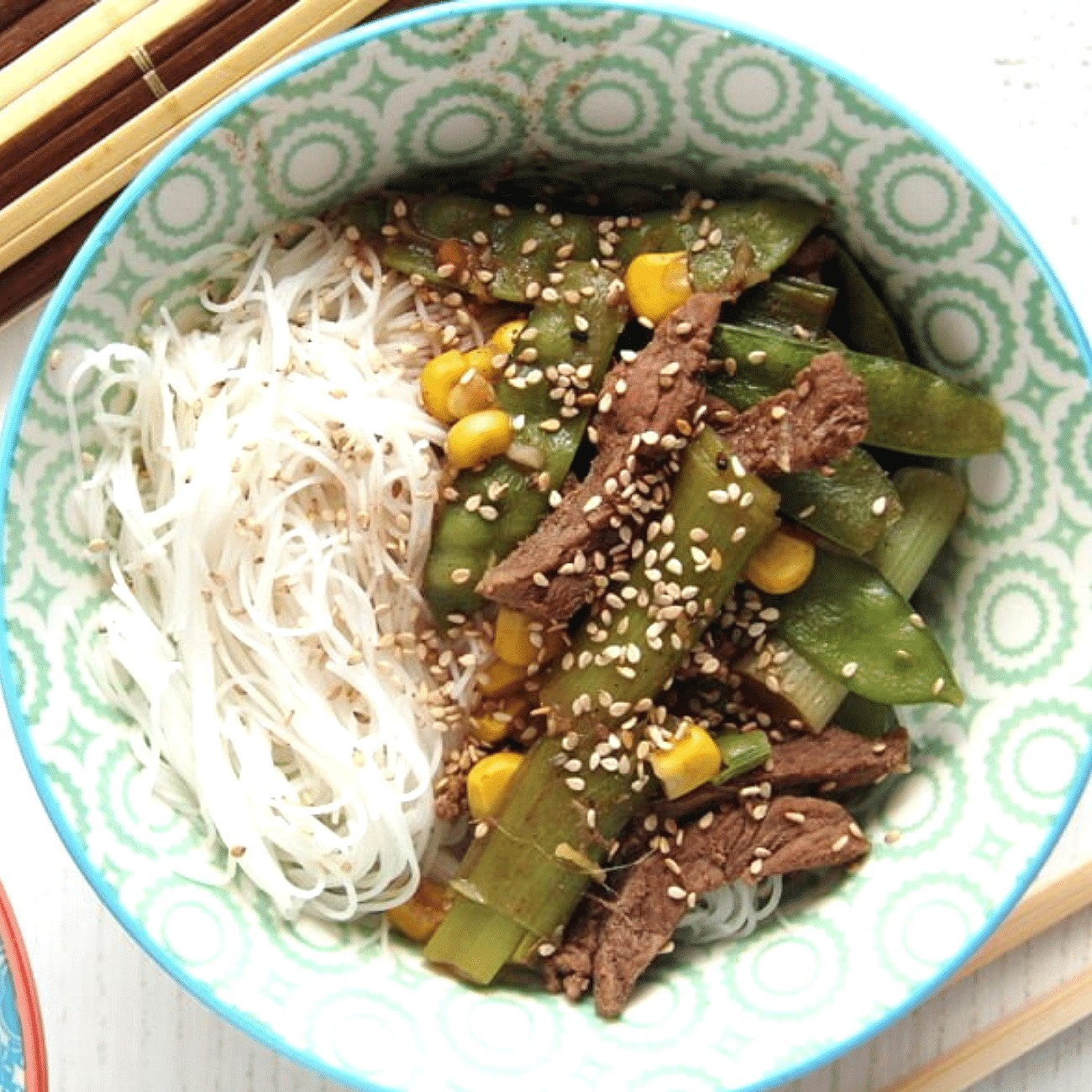 rice noodle beef bowl with green onions and sugar snap peas