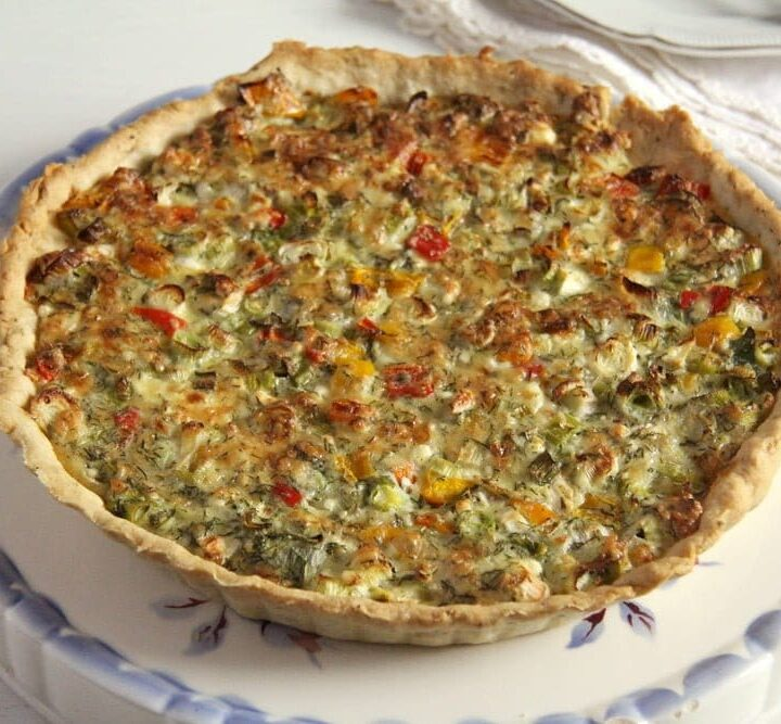 green onion quiche with veggies and cheese on a vintage platter with blue edges.