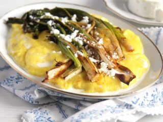 roasted green onions on a platter with polenta and cheese