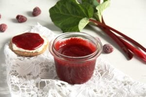 low sugar rhubarb raspberry jam in a jar and on crispbread