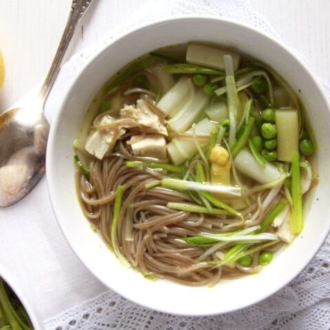 spring soup recipe with soba noodles and chicken in a white bowl