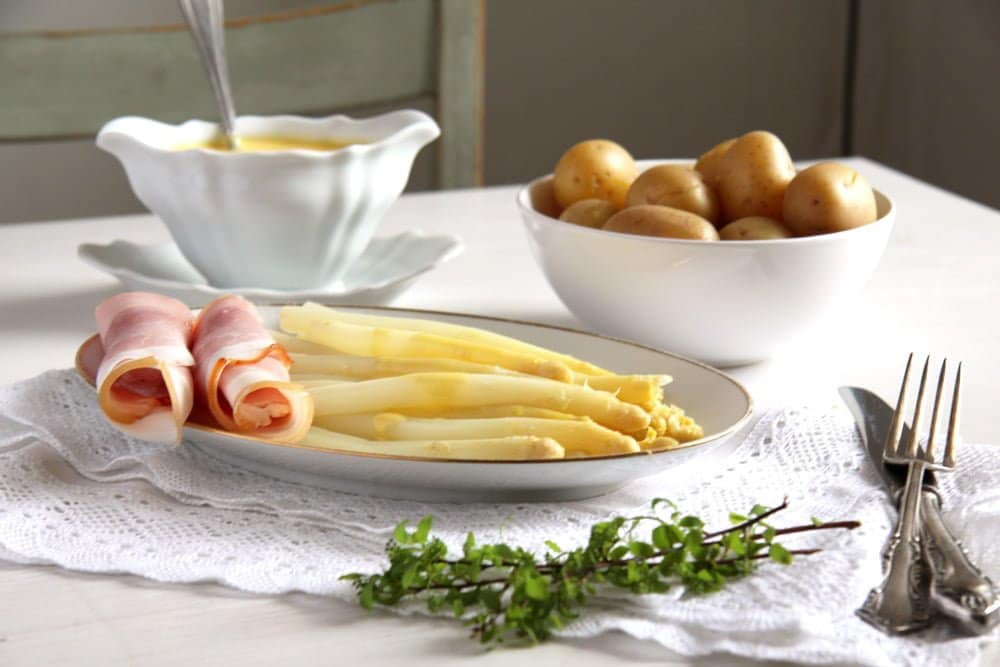 platter with white asparagus, ham, white sauce and potatoes