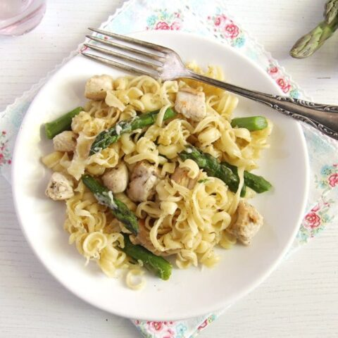 dish full of noodles, chicken pieces and green vegetables