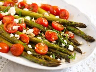 plate of roasted green asparagus with cherry tomatoes and feta