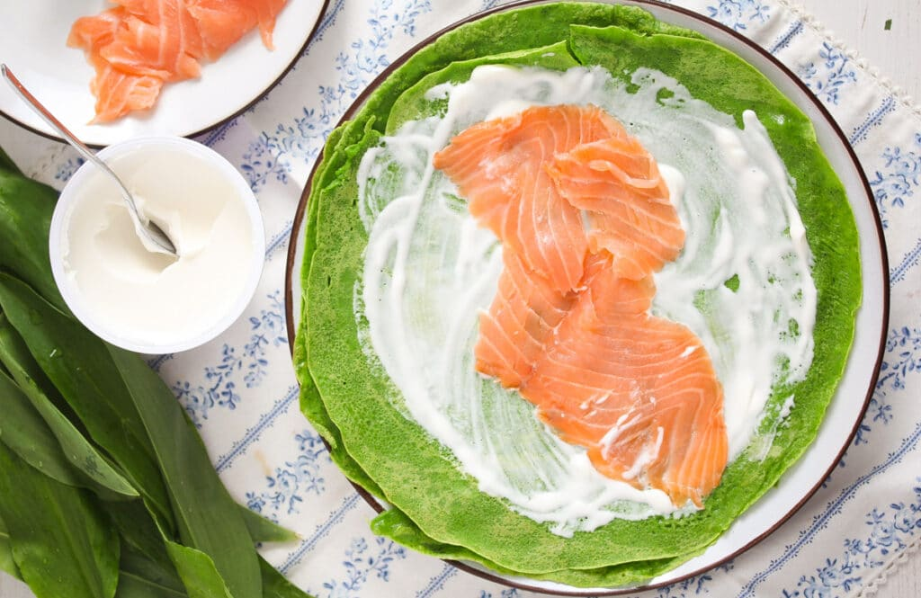 filling crepes with creme fraiche and salmon slices