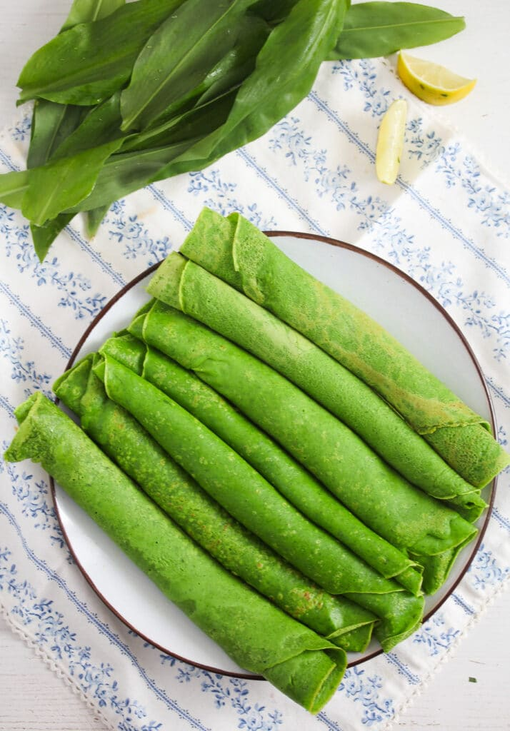 rolled green crepes on a large plate on the table