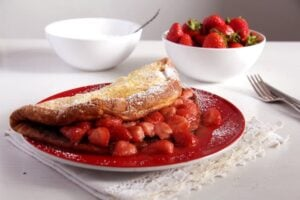 close up strawberry filled thick large pancake on a plate