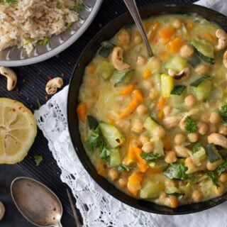 zucchini curry recipe served in a black bowl with lemon beside