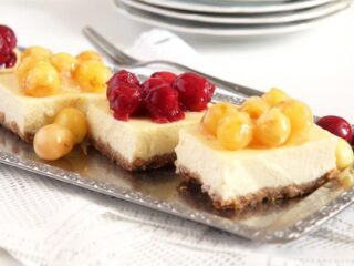 cake slices topped with red and yellow cherries