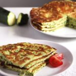 courgette pancakes on a plate with tomatoes