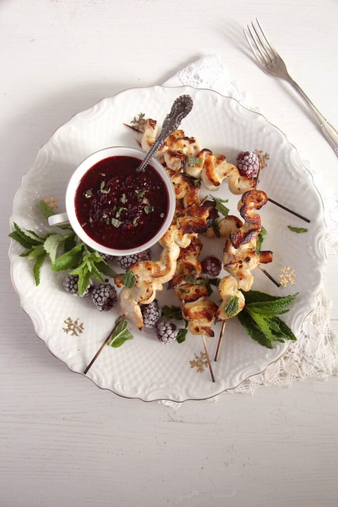 plate with chicken skewers and a bowl of blackberry sauce