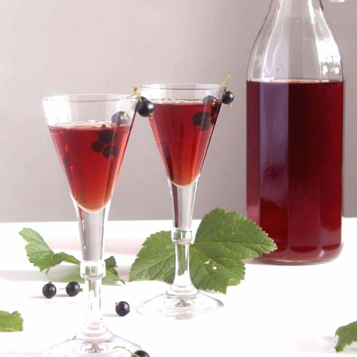 homemade creme de cassis recipe in two small glasses and in a bottle