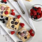 marzipan pastries with berries and almonds on a long platter