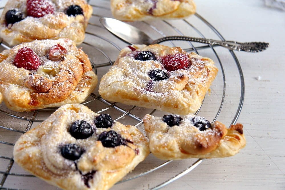 marzipan pastries with puff pastry and berries on a cooling rack
