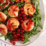 large shrimps covered in red sauce on salad leaves