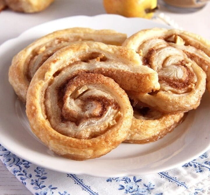 apple puff pastry rolls with cinnamon on a small white plate