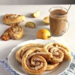 pastries with apples and cinnamon with coffee behind