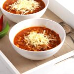 bowls of tomato and beef soup with cheese