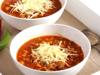 cheesy pizza soup with beef and cheese on top