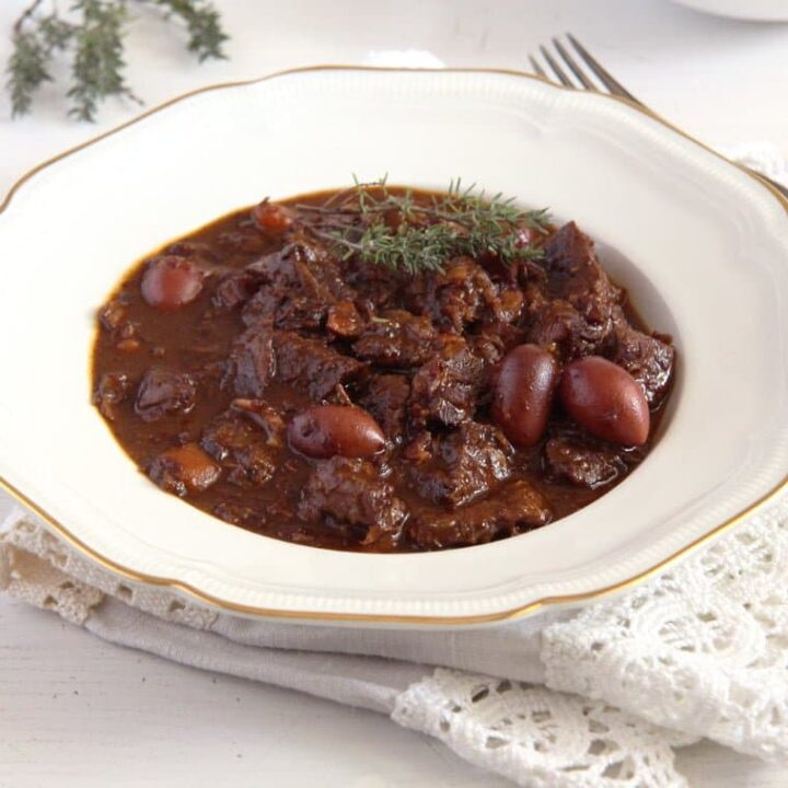 beef stew with red wine and olive on a white plate