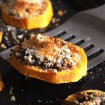 lifting a loaded roasted squash slice off the baking tray
