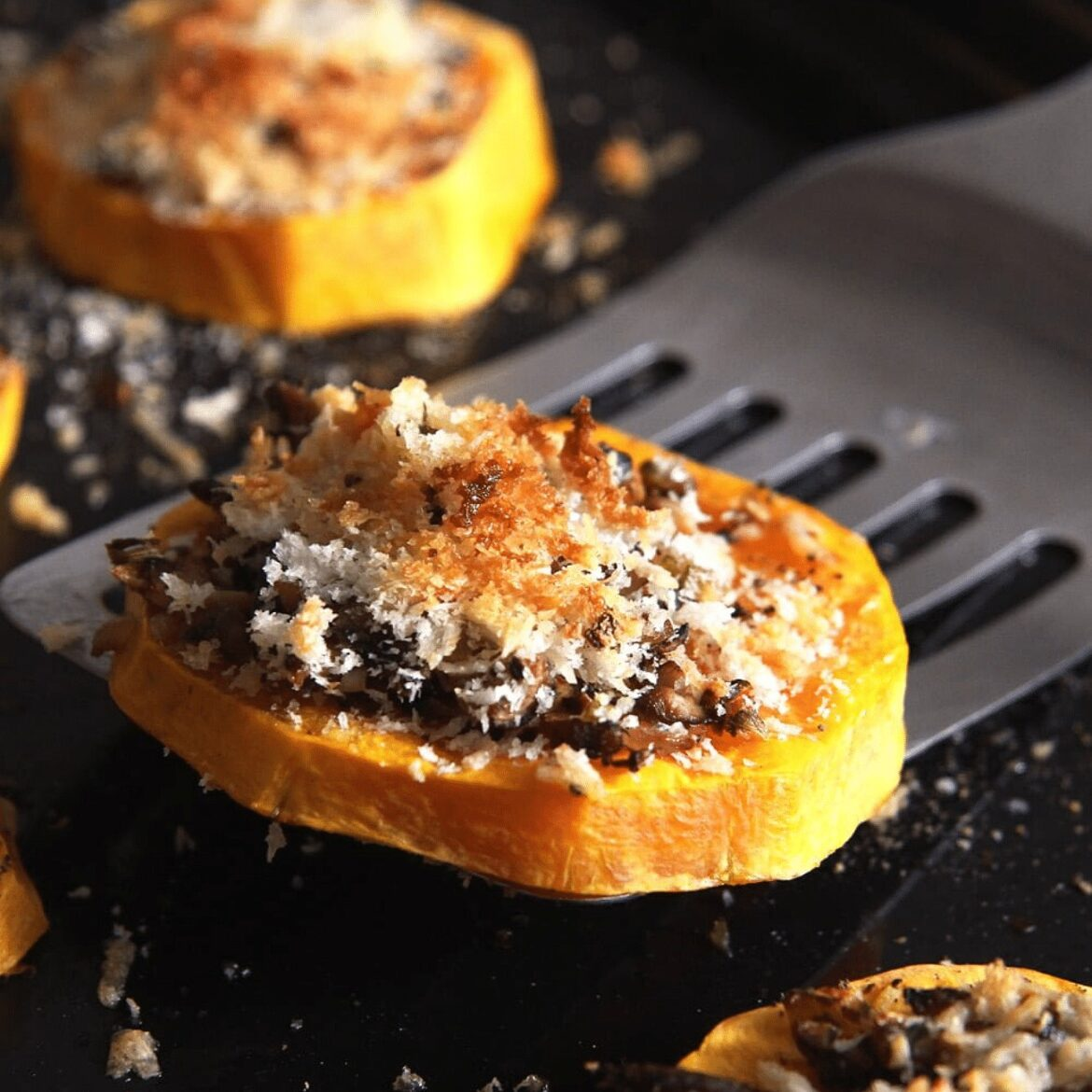 roasted butternut squash slice being lifted from the tray