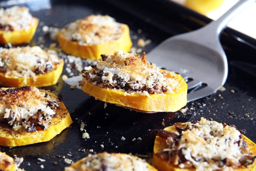 roasted squash slices with parmesan on a black baking tray