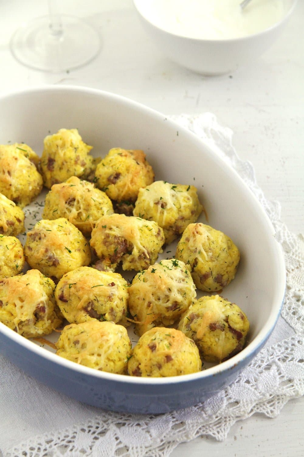 cheesy balls with cornmeal and sausages in a blue baking dish
