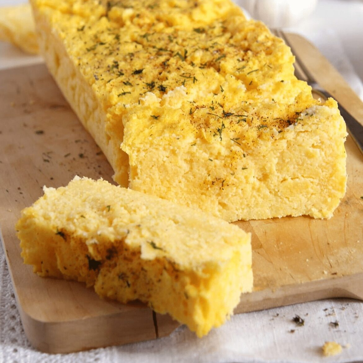 polenta loaf sliced on a wooden board