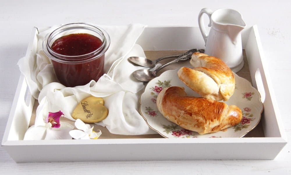 breakfast tray with croissants, jam, chocolate and milk