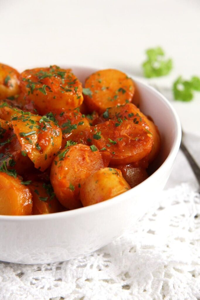 new potato slices with tomato sauce and parsley in a bowl