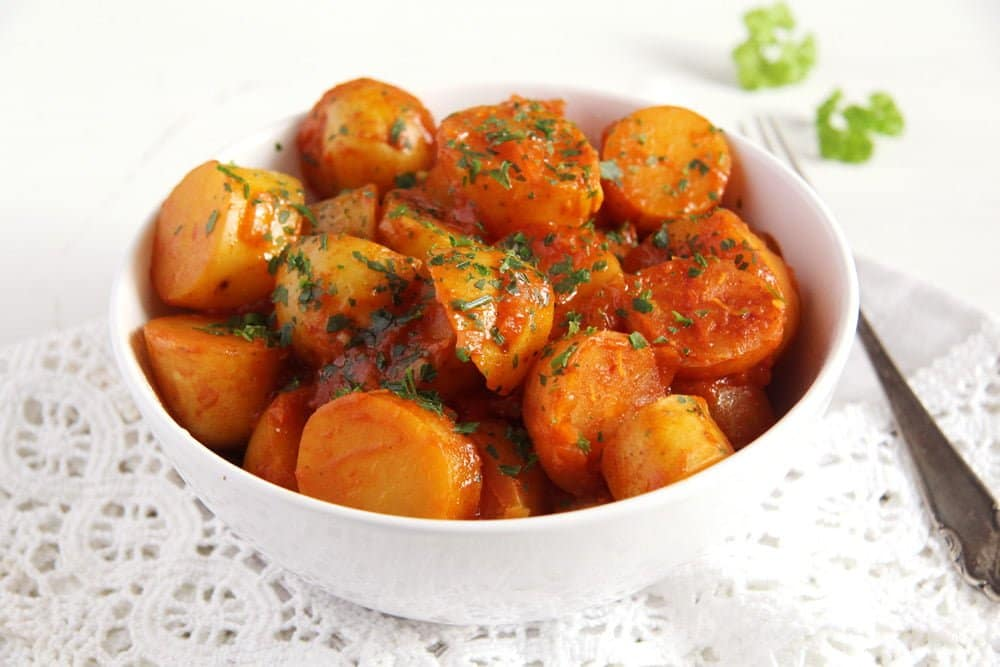 potatoes with tomato sauce in a white bowl