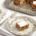 biscuit apple cake sprinkled with icing sugar on vintage dishes.