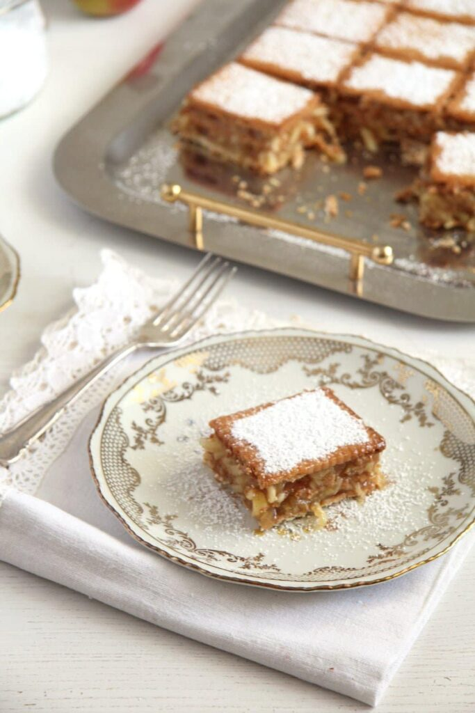 biscuit apple cake sprinkled with icing sugar on vintage dishes