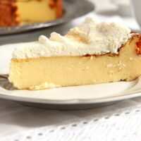 easy crustless cheesecake with whipped cream sliced on a small vintage plate.