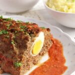 beef meatloaf with egg in the middle cut on a platter.