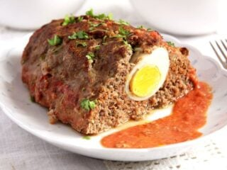 meatloaf with eggs served with tomato sauce on a platter.