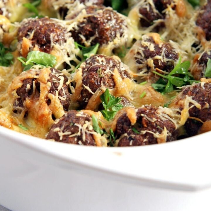 meatball potato casserole with cheese and parsley in a white oven dish