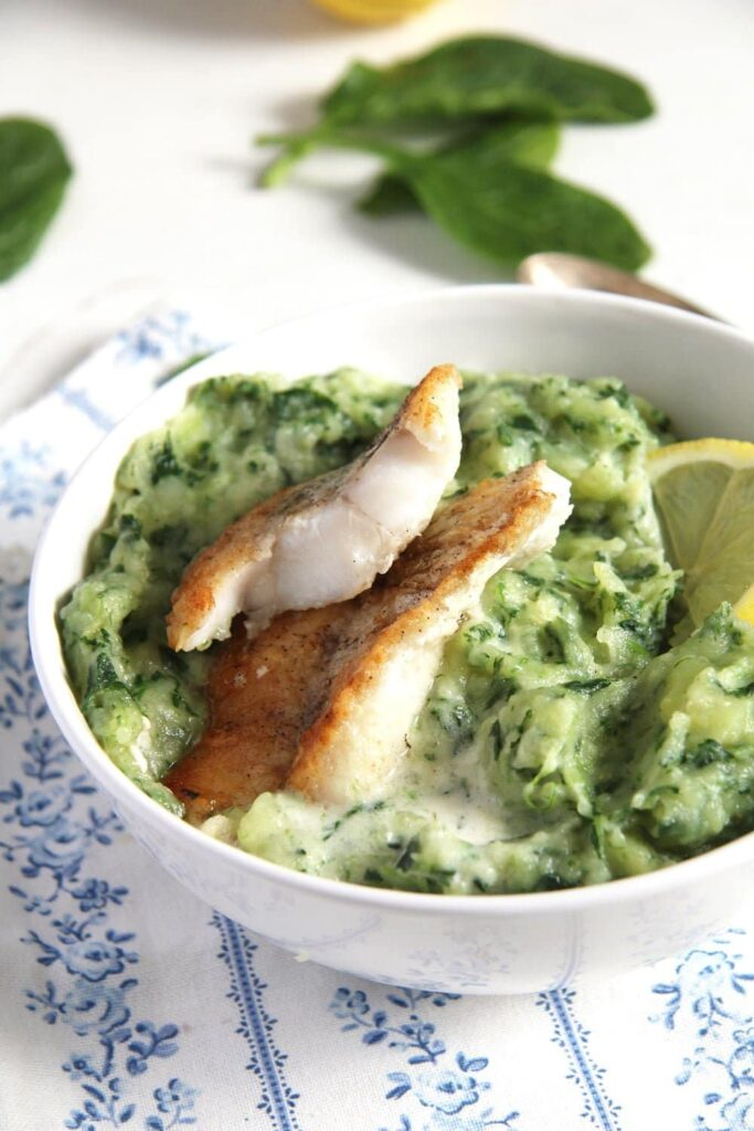 spinach mashed potatoes with fish in a bowl