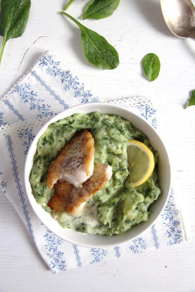 Spinach potato mash with fish and lemon in a bowl