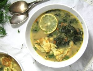 spinach soup with eggs in a white bowl served with lemon slices