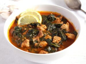 pork and spinach recipe with tomato sauce and lemon in a bowl