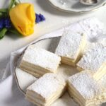 layered romanian lemon cake sliced on a plate with a yellow tulip behind