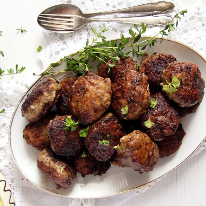romanian meatballs or chiftele on a vintage platter sprinkled with herbs