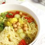 turmeric vegetable soup with noodles and chickpeas in a white bowl