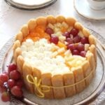 charlotte torte with whipped cream and fresh fruit on a platter