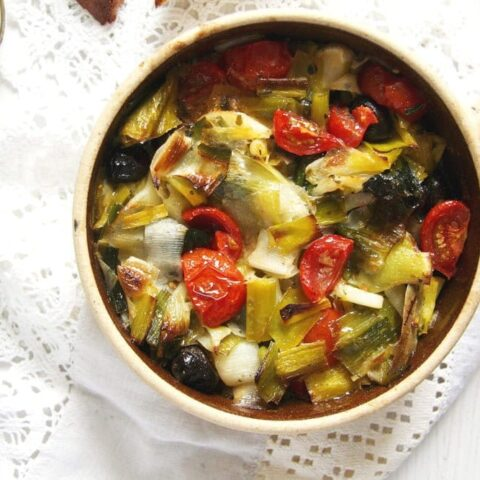 small clay pot with leeks, tomatoes and black olives