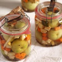 jars with green pickled tomatoes