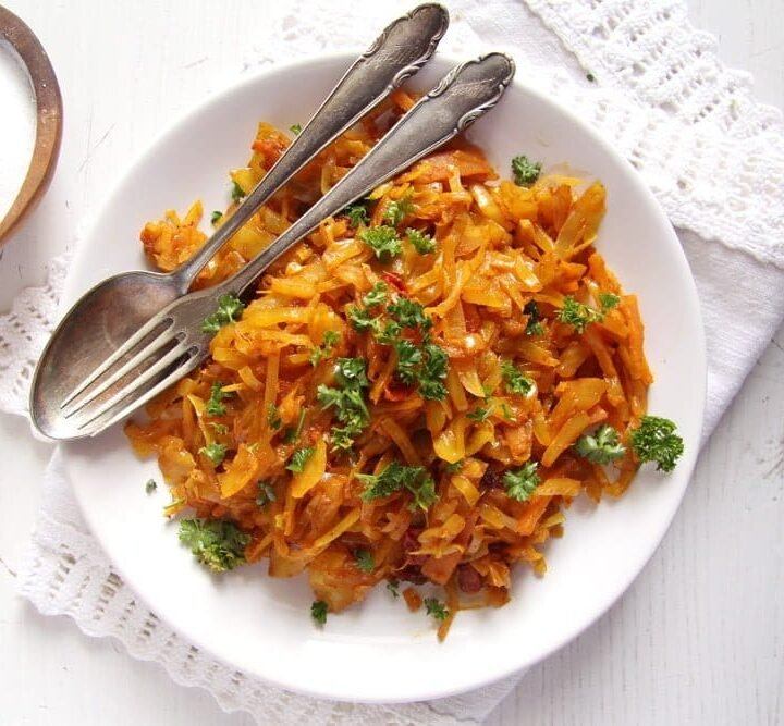 turmeric cabbage stew on a plate with fork and spoon