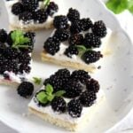 cake slices topped with beautiful fresh blackberries and mint leaves
